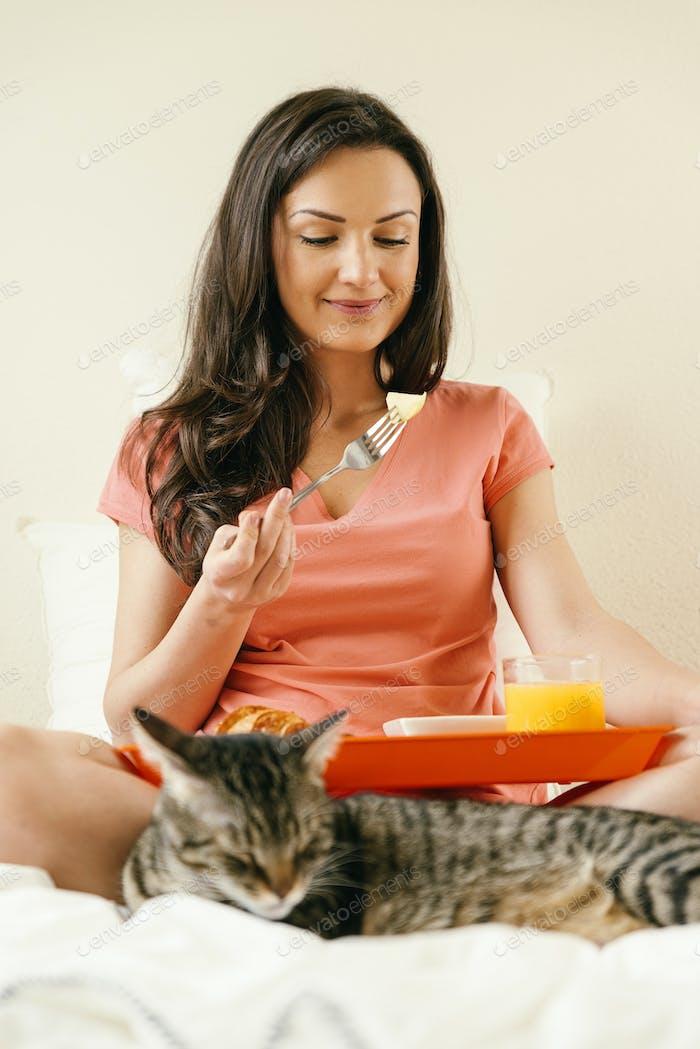 Happy woman having breakfast in her bedroom.
