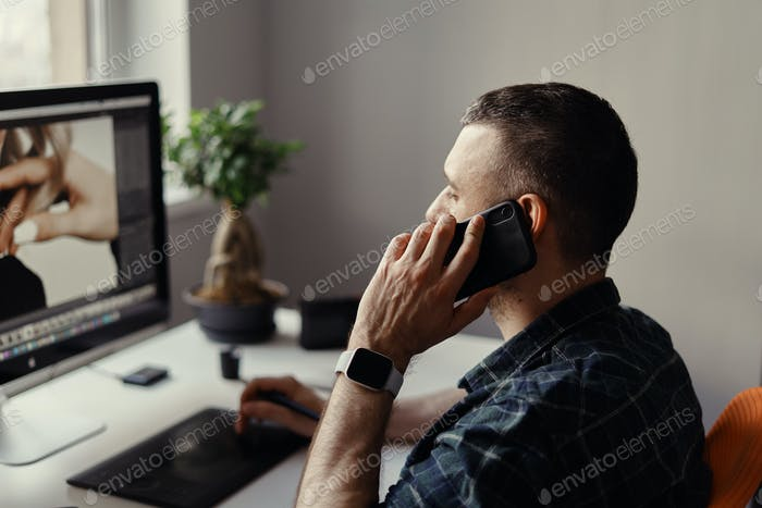 Modern man speak on phone while working on computer