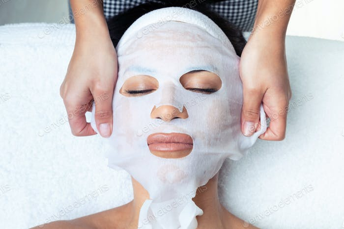 Cosmetologist making the vitamin C facial mask for rejuvenation to woman on the spa center.