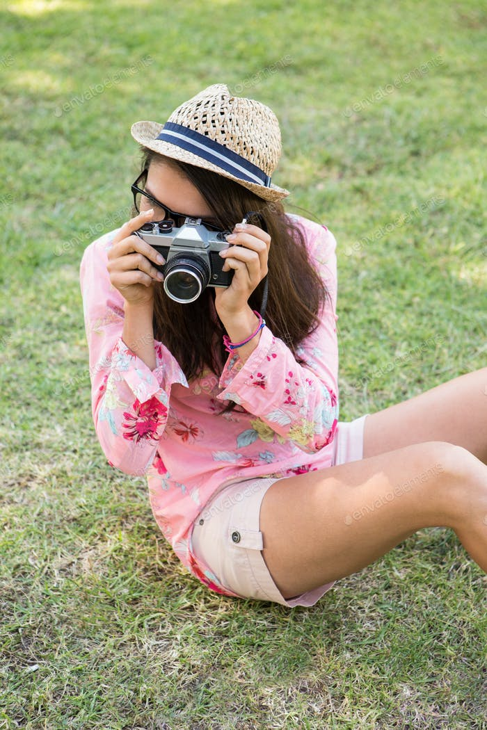 Pretty brunette with retro camera on a summers day