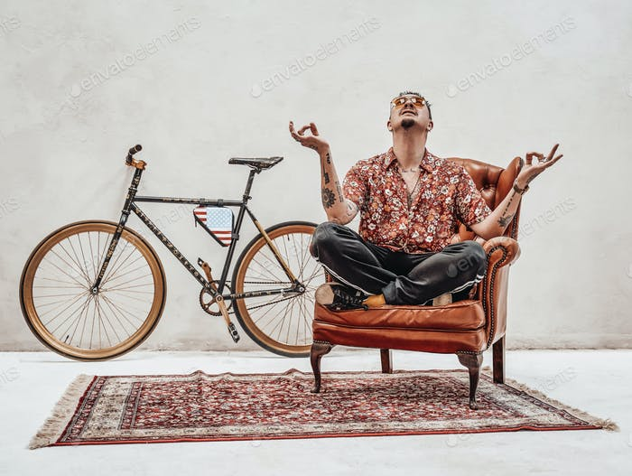 Tattooed stylish gangster sits on a armchair in a lotus pose, looks very expressive and freakly