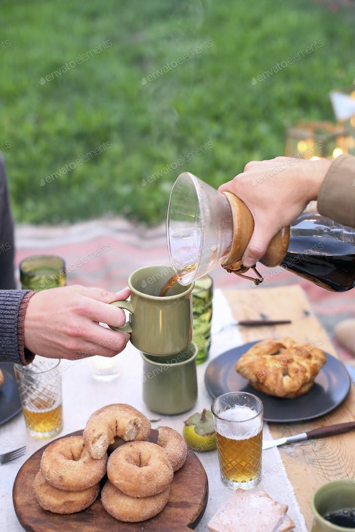 Apple orchard. Two people sitting at a table with food and drink, pouring coffee.