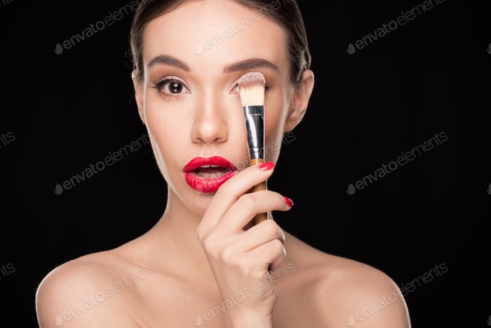 Young surprised woman holding makeup brush and looking at camera isolated on black