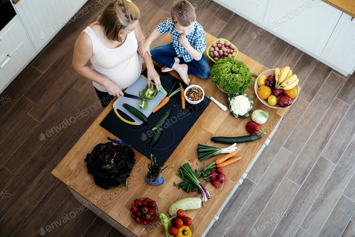 Pregnant mom and child preparing meal