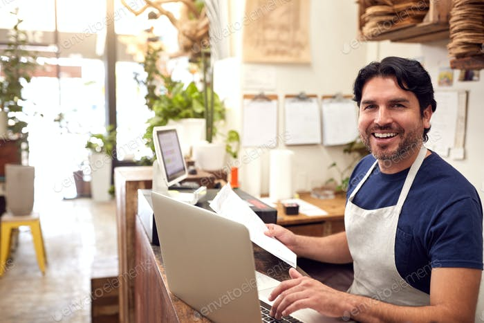 Portrait Of Male Sales Assistant Working On Laptop Behind Sales Desk Of Florists Store