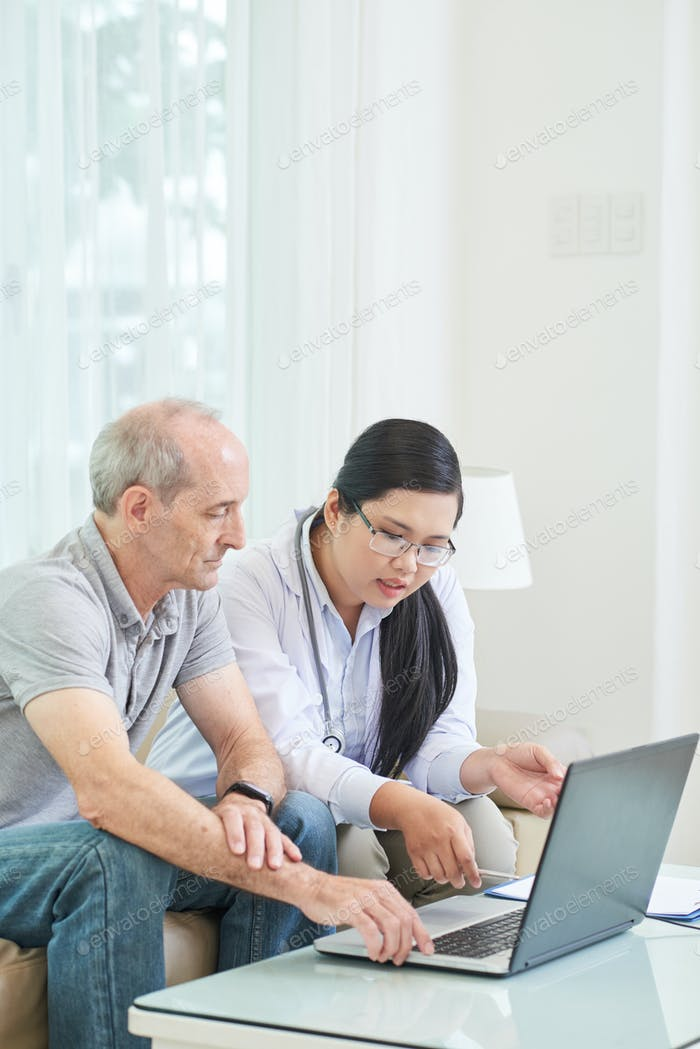 Senior patient with woman watching laptop