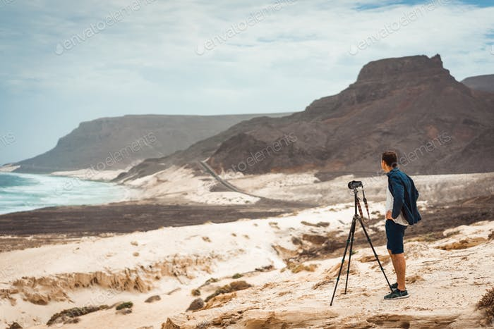 Thumbnail for Photographer with camera in desert admitting unique landscape of sand dunes volcanic cliffs on the