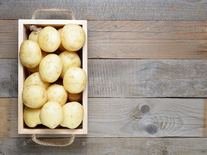 Картофель в деревянной коробке на столе сверху