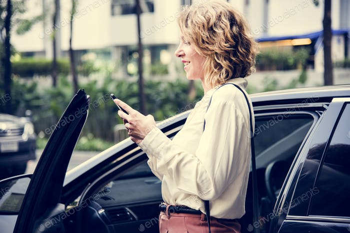 Woman texting before getting into the car