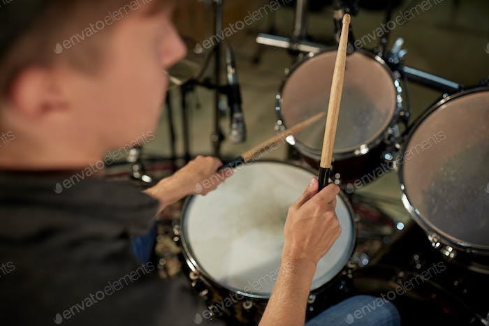 man playing drums at concert or music studio