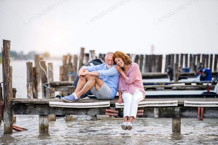 Senior couple on a holiday sitting by the lake, hugging