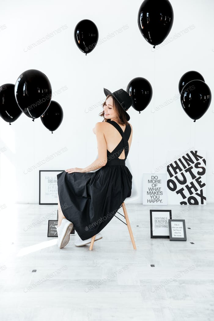 Woman sitting over white background with black posters and balloons