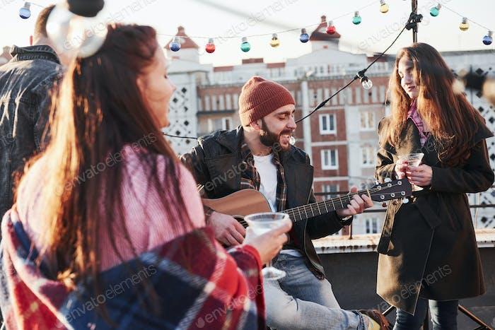 Chillt aus. Junge Freunde feiern mit Alkohol und Gitarre auf dem Dach