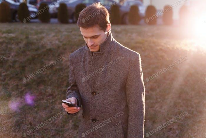 Ein hübscher junger Geschäftsmann mit seinem Telefon und steht am Abend auf der Straße