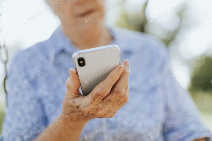 Senior woman listening to music through headphones