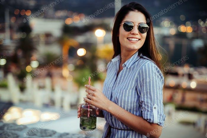 Schöne junge glückliche Frau lächelnd und trinken Cocktail