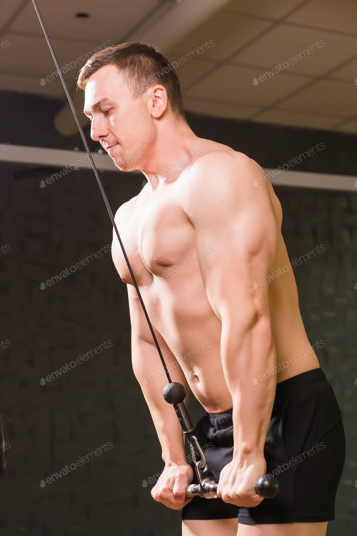 Handsome young muscular man training in the gym.