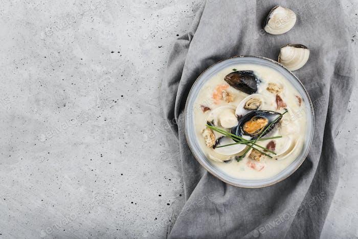 Muschelsuppe in einer grauen Platte. Die Hauptzutaten sind Schalentiere, Brühe, Butter, Kartoffeln