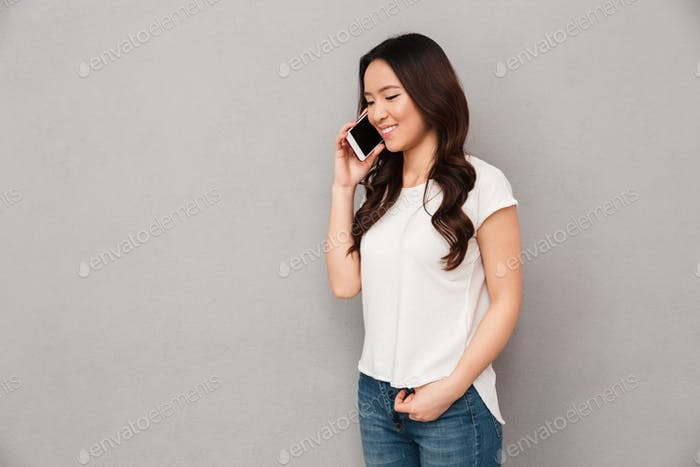 Modern asian woman in casual t-shirt and jeans having mobile cal