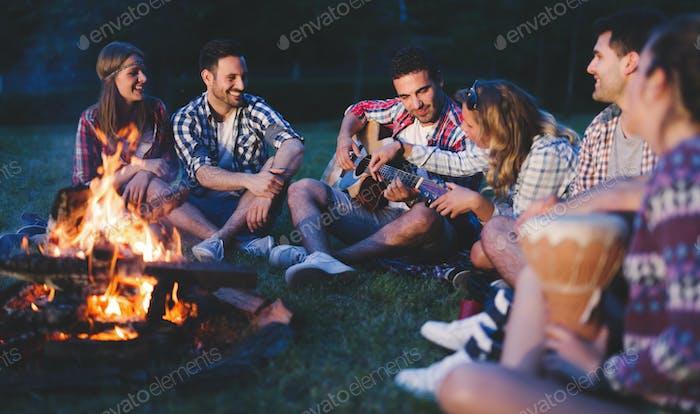 Happy friends playing music and enjoying bonfire