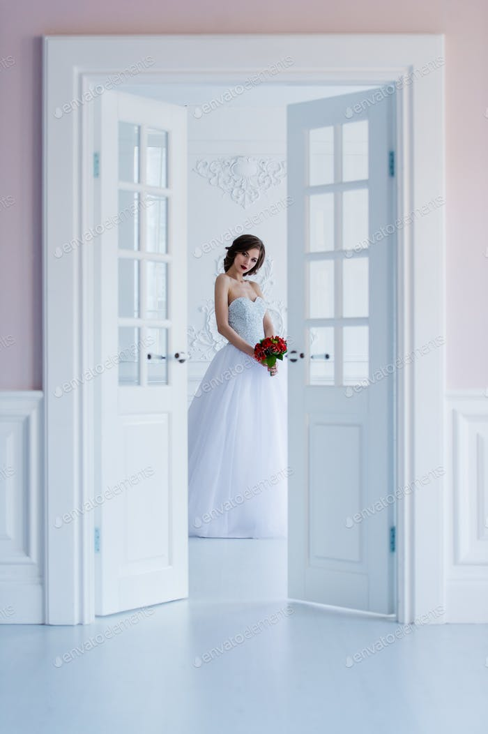 Модное фото красивой невесты в светлой комнате рядом с дверями