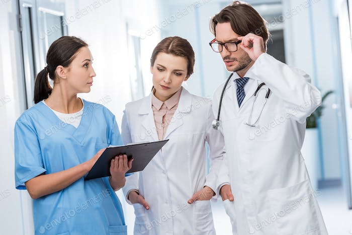 Doctors discussing diagnosis with nurse in clinic