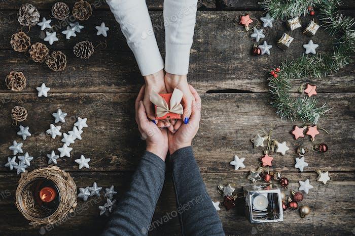 Draufsicht eines männlichen Hände Schröpfen weibliche Hände halten kleine rote Feiertags-Geschenk-Box