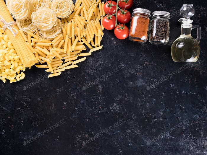 Variety of uncooked pasta next to spices, fresh tomatoes and sunflower oil