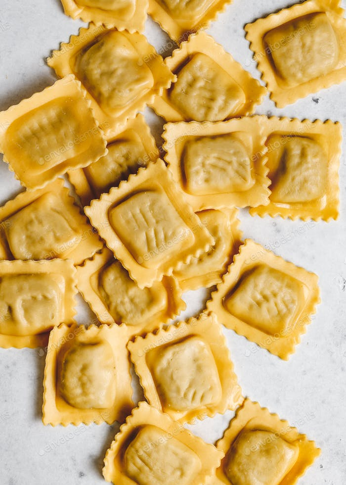 View from above on homemade raw Italian ravioli pasta on a white background.
