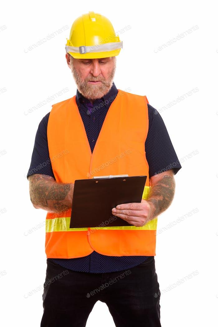 Reifen bärtigen Mann Bauarbeiter Lesen auf clipboard