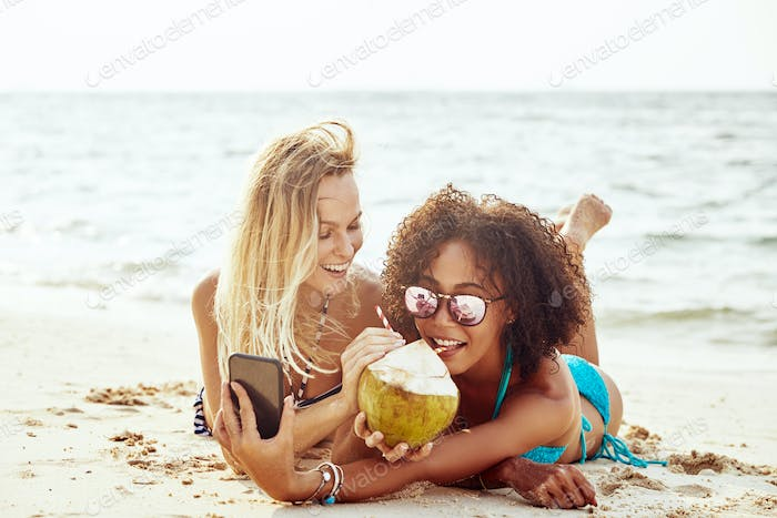 Suntanning friends taking selfies together on a tropical beach