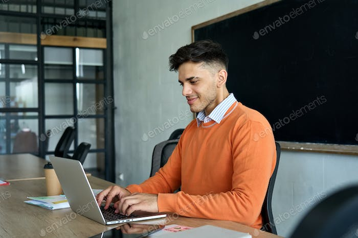 Latin Indian young programmer student sitting using laptop at modern office.