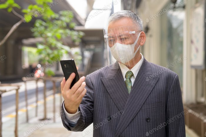 Mature Japanese businessman with mask and face shield using phone in the city
