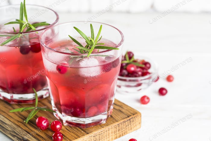 Cocktail with cranberry, vodka, rosemary and ice
