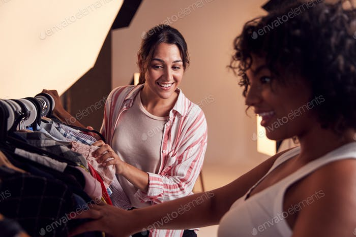 Stylist Discussing Wardrobe With Female Photographer On Fashion Shoot In Studio