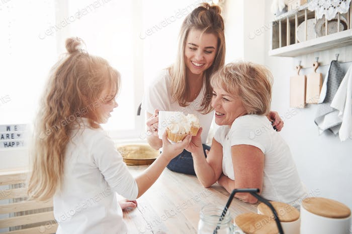 Mother, grandmother and daughter having good time in the kitchen