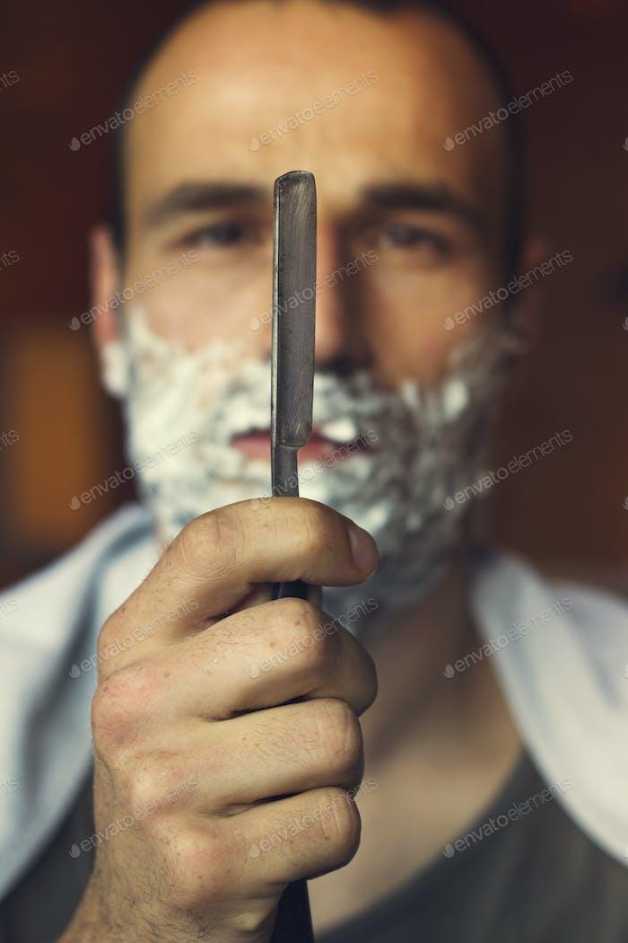Young man holding straight razor