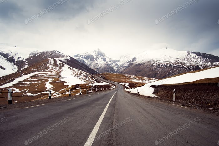 Winter Road Stretching Into The Distance Among The Mountains And Cloudy Sky