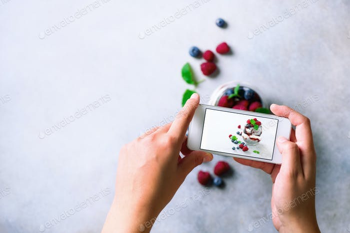 Girl is taking photos of breakfast, chia pudding with berries to mobile phone. Social media concept
