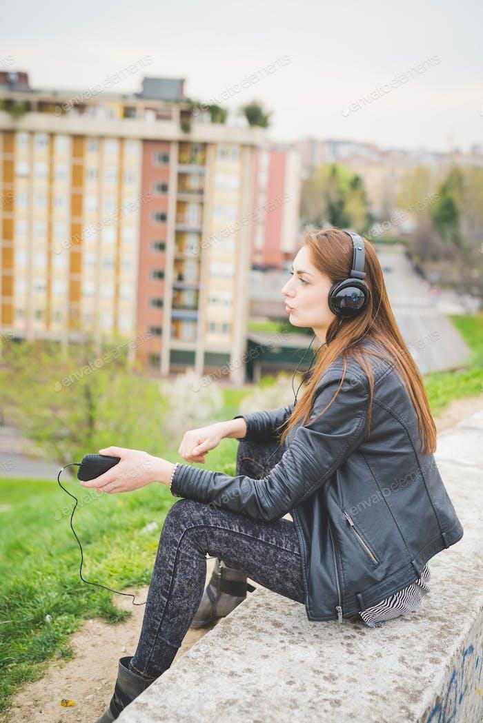 Young handosme brunette girl listening music