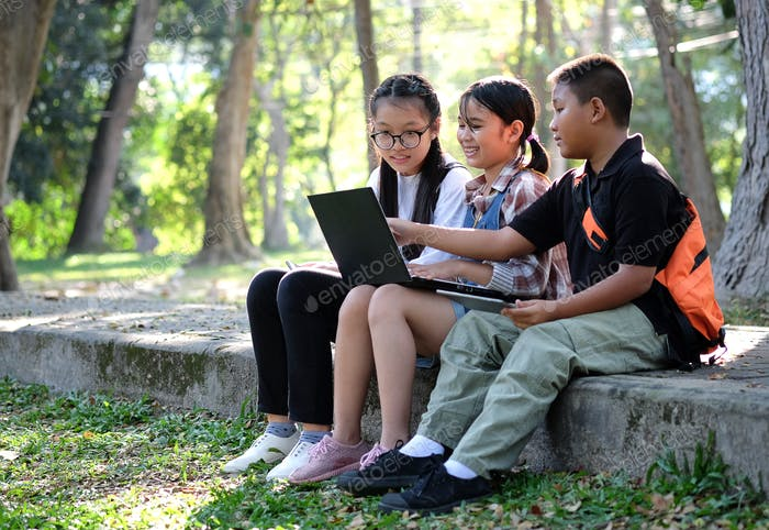 Three asian boy and girls playing laptop in garden.