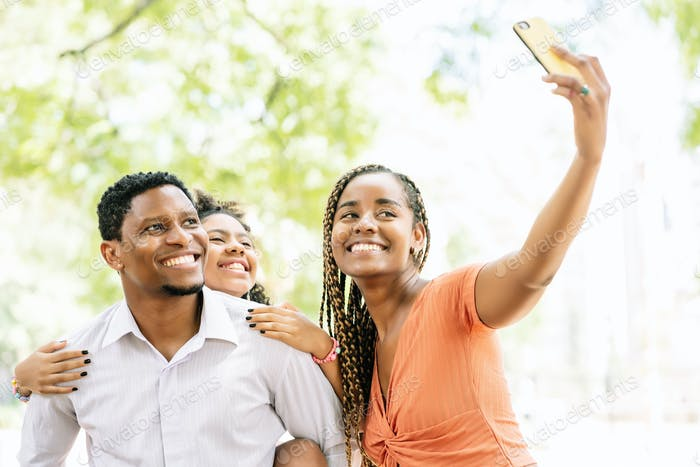 Family taking a selfie with a mobile phone at the park.