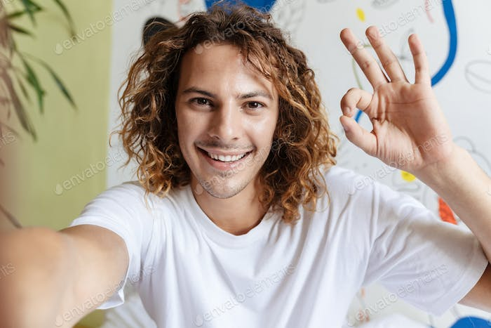Caucasian handsome smiling guy gesturing ok sign and taking selfie