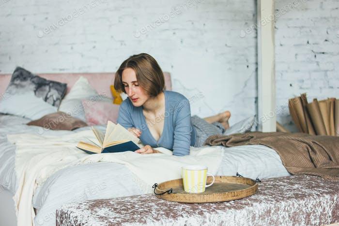 Junge Frau lesen Buch auf dem Bett im Dachboden Zimmer