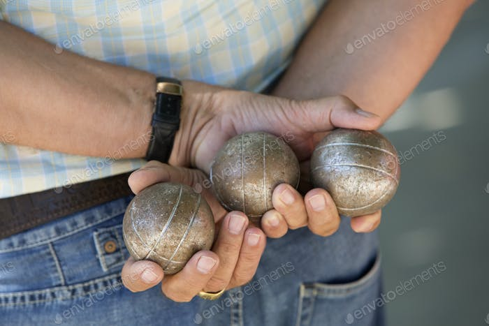 A boules player holding three metal boules in his hands behind his back.