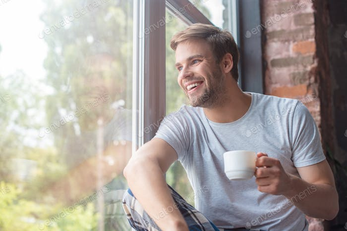 smiling man looking in windows and sitting with cup of coffee on windowsill