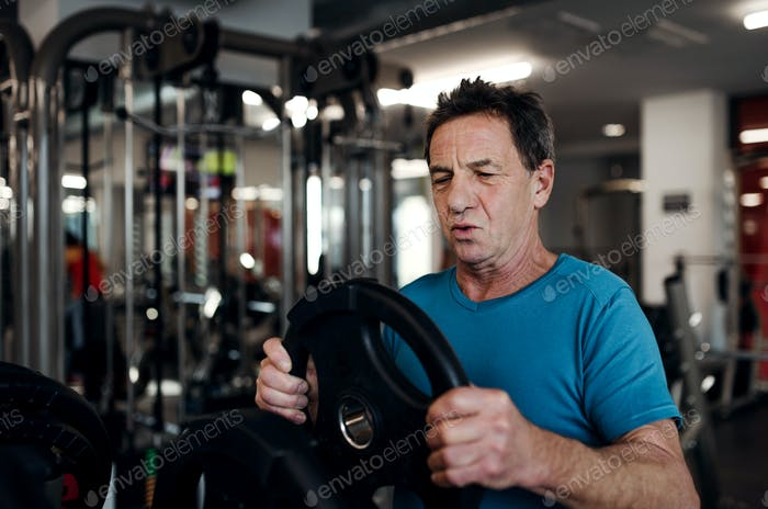 A senior man doing strength workout exercise in gym. Copy space.