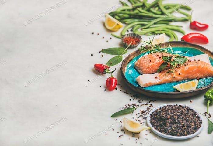 Rohe Lachssteaks mit Gemüse, Reis in hellblauen Teller