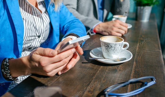 Hands of business woman and man having coffee