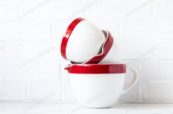 Bowls for mixing ingredients and making dough. Red-white on a brick wall background.